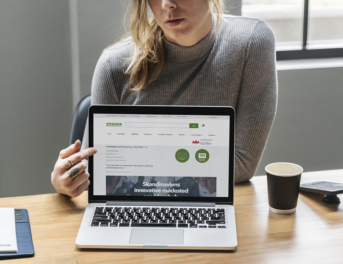 Woman showing a laptop screen mockup